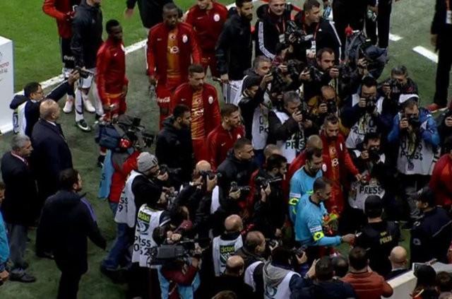 Daha sonra oyuncular, saha kenarında bulunan polislere karanfil verdi.