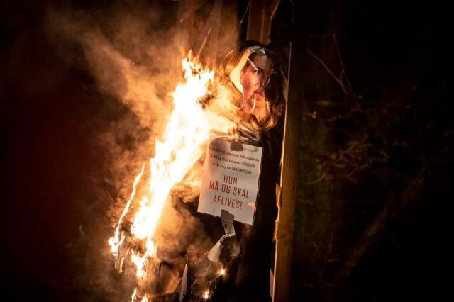 """Bu hafta sonu Kopenhag'da düzenlenen bir gösteri sırasında, Danimarka Başbakanı Mette Frederiksen'i temsil eden bir oyuncak maket yakıldı.   Hükümete saldırı şüphesiyle iki kişi tutuklandı.  Maketin üzerinde başbakan için """"Öldürülmeli"""" yazan bir slogan vardı.  Kopenhag Emniyet Müdürü Anne Tønnes basın açıklamasında, """"Bir demokraside böylesine ciddi tehditler yapmak asla kabul edilemez, bu yüzden yürütülen kapsamlı soruşturmanın zaten davada tutuklamalarla sonuçlanmasından çok memnunum."""" ifadeleri kullandı."""