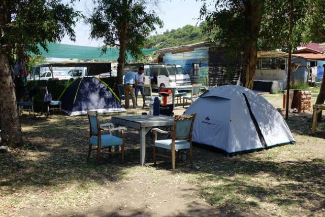 """Kendi çadırı olmayanlar için 60 krondan başlayan ve kurulan alana, çadırın özelliklerine göre 160 krona kadar çıkan bu alternatif tatili tercih edenler, deniz kıyısında dalgaların sesiyle uyuyor, sabahları ormanlık alanların içinden gelen kuş sesleriyle uyanıyor.  Etrafı tel örgülerle çevrili ve çoğunda güvenlik kamerası da bulunan çadır kamp alanlarına gelenler, kendi yemeklerini yapıyor, elektrik için günlük sadece 10 kron ek ücret ödüyor.  Balıkesir'in Burhaniye ilçesi Ören Mahallesi sahilinde çadır kamp alanı işleten Filiz Altın, AA muhabirine yaptığı açıklamada, yıllardır işlettikleri alanın genellikle yerli turistlerce tercih edildiğini söyledi.  Çadır kampa gelenlerin sakin ortamları isteyenler olduğunu bildiren Altın, şöyle konuştu:  """"Doygun bir yeşilin içinde mavi deniz, cıvıl cıvıl kuş sesleri, cırcır böceği ve deniz dalga sesleri eşliğinde kitap okumak için geliyor. Kampı belli bölgelere ayırdık ve her keseye uygun olacak şekilde fiyat kategorileri yaptık. Mesela denize sıfır olan bölüm var, orta bölüm var, garden bölümü var. Düşüncemiz kimseye pahalı gelmesin ve herkes burada tatil yapabilsin. Fiyatlara gelince iki kişi kendi çadırıyla gelirse 110 krona geceleme ücretidir. Bu rakam deniz kıyısından uzakta ormanın içinde fiyat. Bizim çadırlarımızda kalırsa, denize yakın olursa bu rakam iki kişi için çadırın boyutuna göre 120 ile 160 krona çıkıyor."""""""