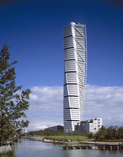 """Turning Torso binasına bakıp nasıl sapasağlam ayakta duruyor diye soranları daha fazla bekletmeyelim: Cevap asansör! Binanın merkezinde yer alan ve ekseni belirleyen asansör boşluğu aslında çelik bir boru vazifesi görüyor ve yük bu asansörün çevresine dengeli bir şekilde yayılıyor. Bu temel direği, binayı çepeçevre saran çelik konstrüksiyon destekliyor. Dünyanın """"ilk burgu gökdeleni"""" olma unvanını elinde bulunduran Turning Torso gökdeleni mimari bir akımın da öncülüğünü yapmış.  Fotoğraflar: En Son Haber"""