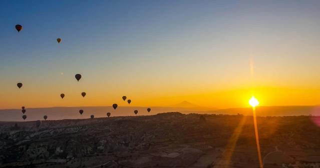 Yerli, yabancı binlerce tatilciye yılın her dönemi farklı manzara sunan Kapadokya'yı ziyaret eden turistler, bölgeyi sıcak hava balon turuna katılarak kuşbakışı keşfediyor.