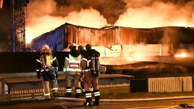 """Hörby'deki itfaiye istasyonu sabahın erken saatlerinde alevler içinde kaldı.  Kurtarma servisinden 16 birim ağır yangına müdahale etmek için çalıştı.  Olay yerindeki kurtarma lideri Daniel Green, en binanın yarısı yanacak, diyor.  Skåne'deki Hörby itfaiye istasyonu sabahın erken saatlerinde yanmaya başladı.  """"İtfaiye binası vagon salonu binasında çok büyük bir yangın var"""" diyen, Kurtarma lideri Daniel Green, """"hasarı sınırlamaya çalışıyoruz, ancak bina yanacak"""" dedi.  Green, söndürme ekipleri gelene kadar istasyonun alevler içinde olduğunu belirtti.  """"Vardığımızda garaj kapılarından birinden alevler çıktı ve çatı bölümünde de yangın çıkmıştı"""" dendi."""
