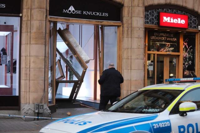 """Başkent Stockholm'ün Norrmalm semtinde bulunan lüks bir giyim mağazasına sabah saatlerinde hırsızlar araçla daldı.  Bu sabah bir araba doğrudan Stockholm'ün merkezindeki lüks bir mağazaya girdi.  Hırsızlık olayını gören bir görgü tanığının soyguncular tarafından silahla tehdit edildiği söylendi.  Edinilen bilgilere göre failler daha sonra mavi bir Mercedes ile kaçtı.  Bölge polis sözücüsü Anders Bryngelsson olayla ilgili açıklamada """"Şu anda güvenlik kamerası olup olmadığına bakıyoruz"""" dedi."""