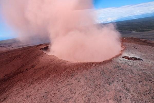 Kilauea'nın ağzından gökyüzüne yoğun bir pembe duman çıkıyor.
