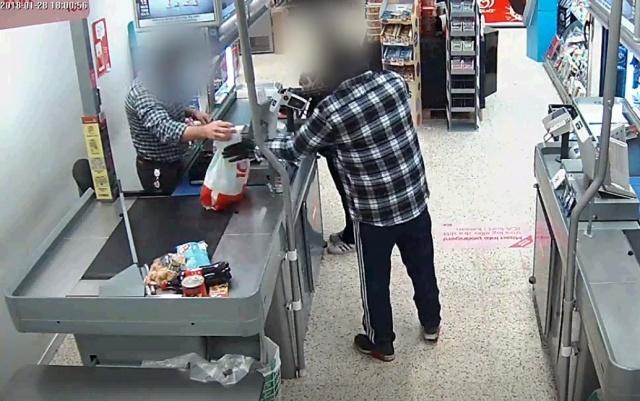 Kasadan poşete doldurulan paraları alıyor soyguncu.