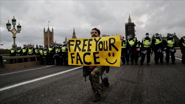 """Eylemcilerin, Başbakanlık binasının önünden geçişi sırasında polisin sıkı güvenlik önlemi alması dikkati çekti.  """"Onayımız yok"""", """"Covid-19 aldatmacası"""", """"Hükümet yalan söylüyor"""" yazılı pankartlar taşıyan göstericiler, Covid-19 önlemlerinin kaldırılmasını istedi."""
