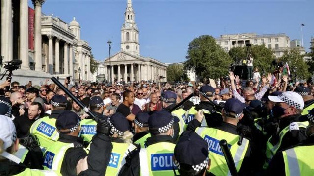 """Başkent Londra'da """"StandUpX"""" üyeleri, Hyde Park'ta bir araya geldi.  Ülkede 6'dan fazla kişinin bir araya gelmesinin yasak olmasına rağmen grup üyeleri, toplu halde yürüyüşe geçti.  Parlamento Meydanı'na yürüyen göstericiler, bir süre sonra Trafalgar Meydanı'na ulaştı."""
